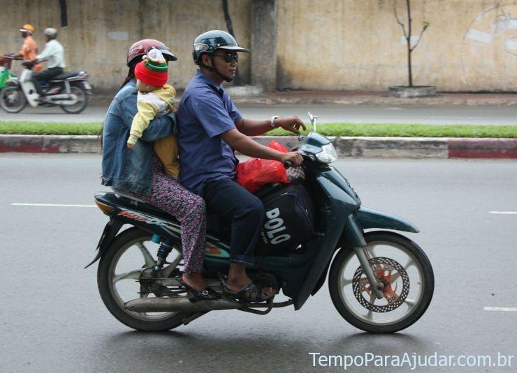 Criança pequena com seus pais na moto